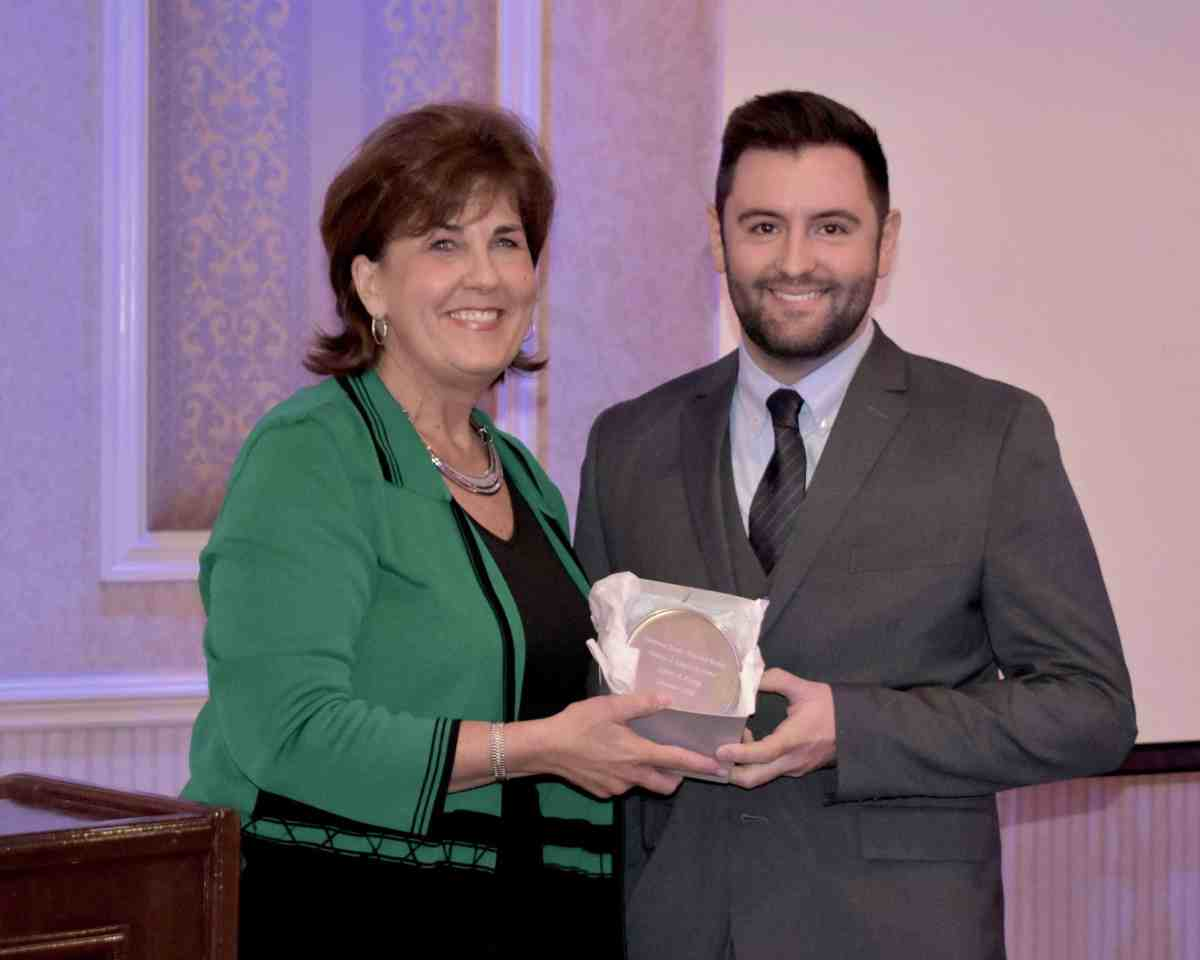 Justin Kemp receives the award from Denise Van Buren.
