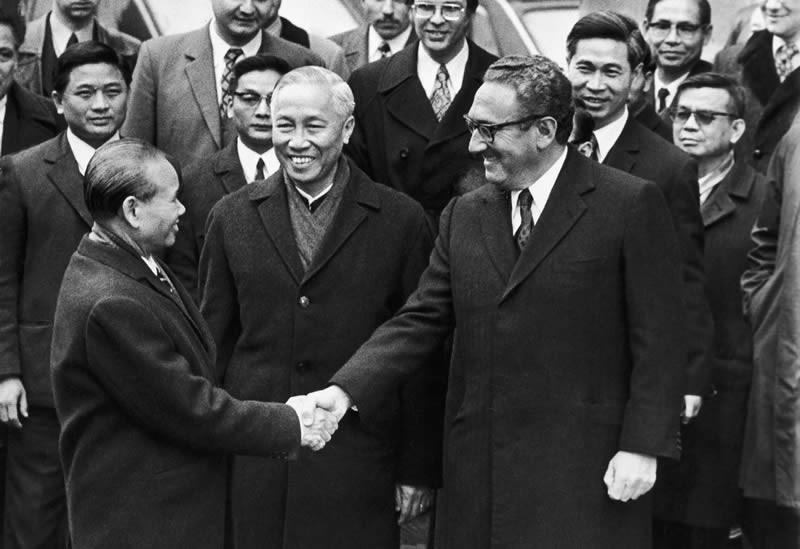 Xuân Thủy bắt tay H. Kissinger. Dứng giũa là Lê Đức Thọ, sau lưng Kissinger là Nguễn Co Thạch. Nguồn:  http://nation-building.jeremisuri.net