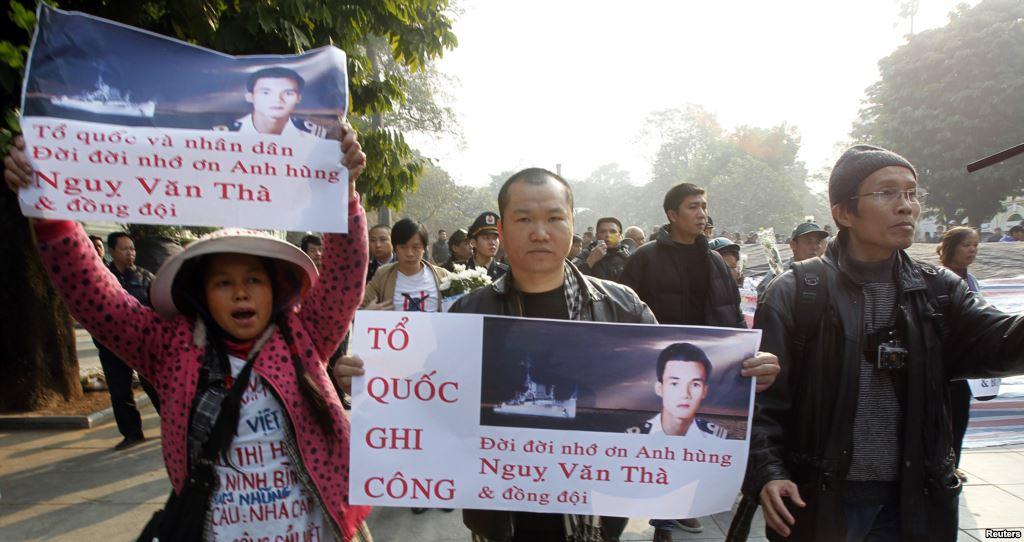 Người biểu tình xuống đường tưởng niệm 40 năm trận hải chiến Hoàng Sa tại Hà Nội với biểu ngữ 'Tổ quốc ghi công, đời đời nhớ ơn anh hùng Ngụy Văn Thà và đồng đội'. Nguồn: Reuters.