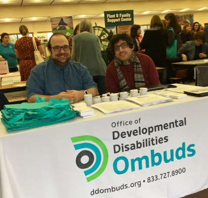 Tim McCue and Noah Seidel sitting at a table that says Office of the Developmental Disabilities Ombuds on it.
