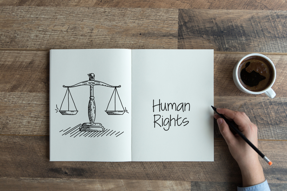"Photo of a notebook showing scales and the words ""human rights"" on a wood table. There is a hand holding a pen and a cup of coffee next to it."