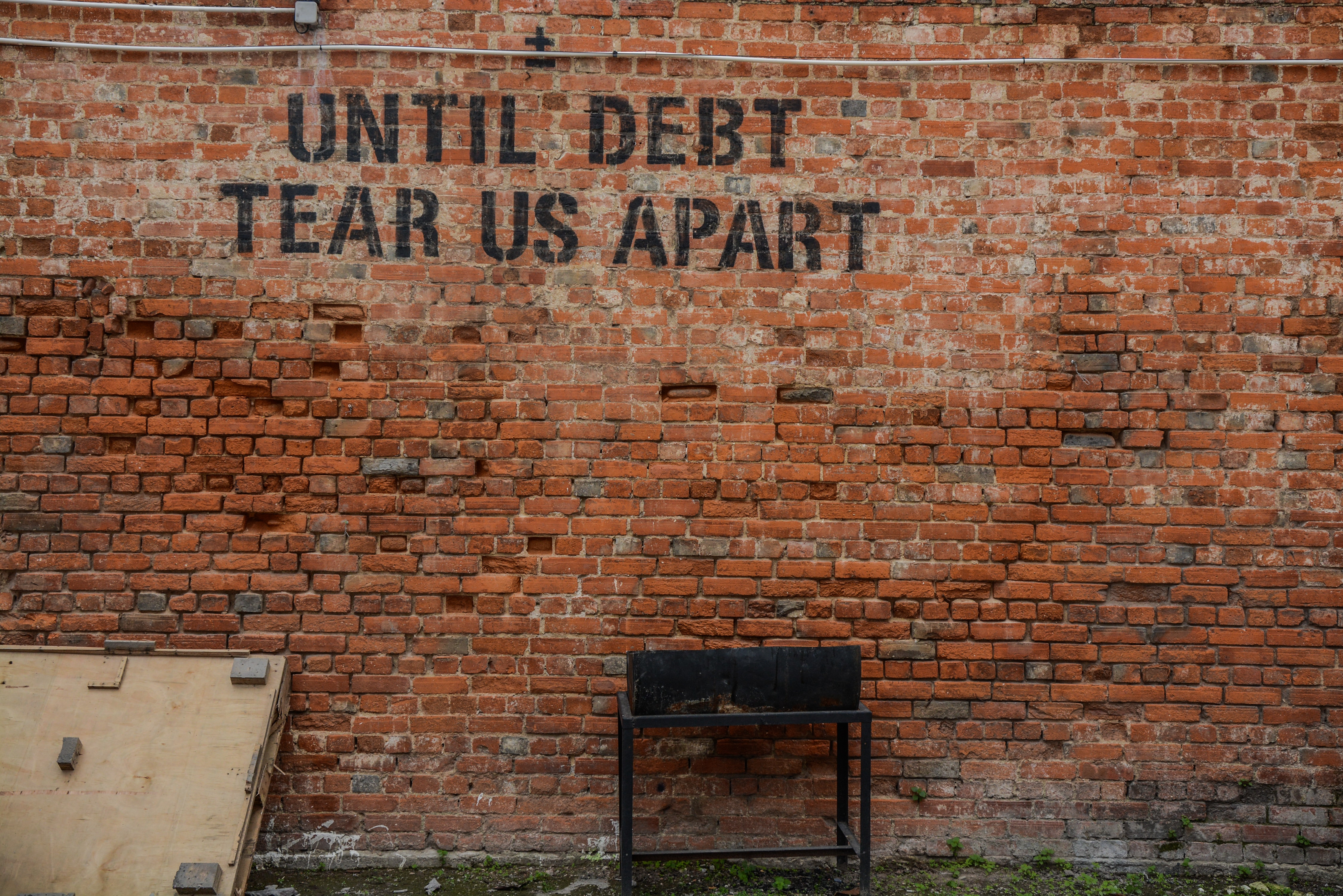 letters printed on a red brick wall - until debt tear us apart