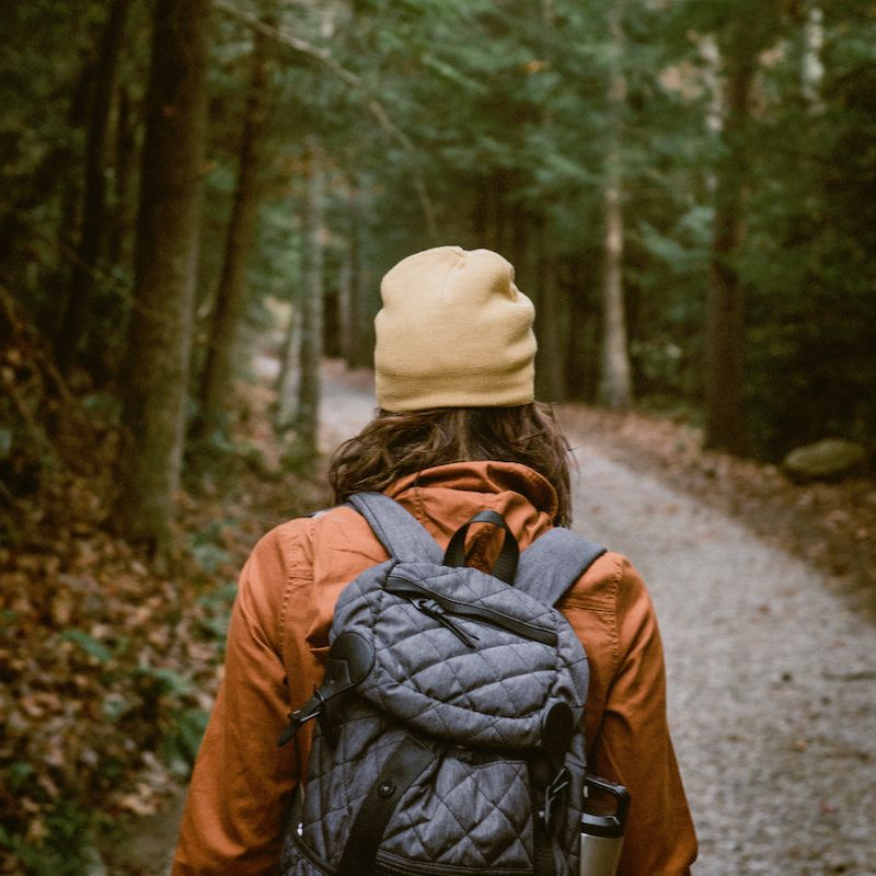 photo of woman hiking in forest