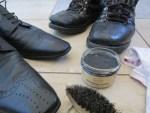 waehrend dem Schuhe pflegen mit schwarzer Schuhcreme