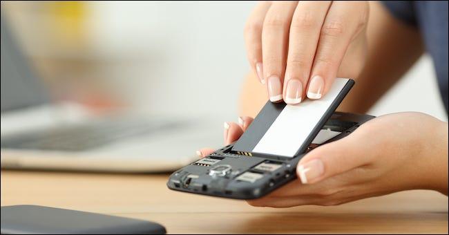 Person, die den Akku von einem Smartphone entfernt