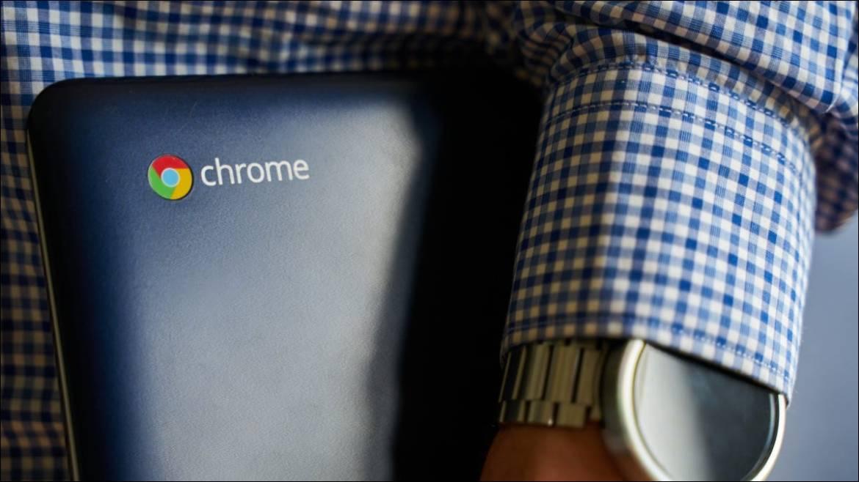 Eine Person, die ein Asus Chromebook unter dem Arm hält.