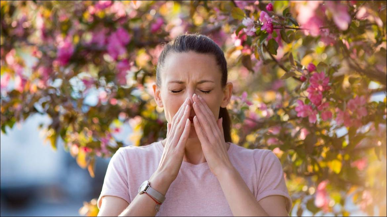 Frau, die unter einem Baum steht und an Pollenallergie niest