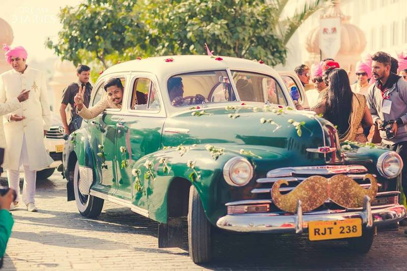 Cool groom entry in a vintage car with moustache sign for a groom with a moustache