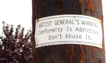 "Sign reading ""Artist General Warning: Confromity is Addictive Don't Abuse it"""