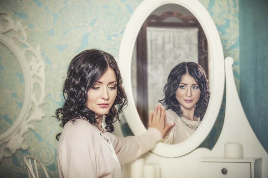 Beautiful woman in the mirror reflected the smiles magically