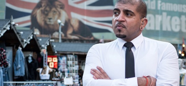 Rinkoo Baparga in shirt and tie looks at a Union Jack Flag above a market place