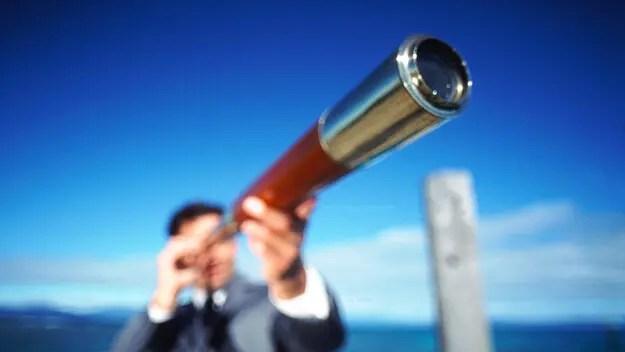 Businessman looking through telescope, defocused