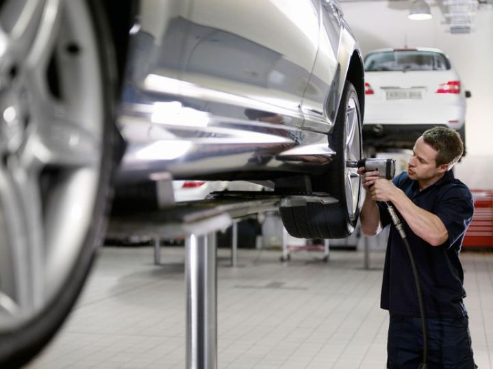 service tech working on car at dealership