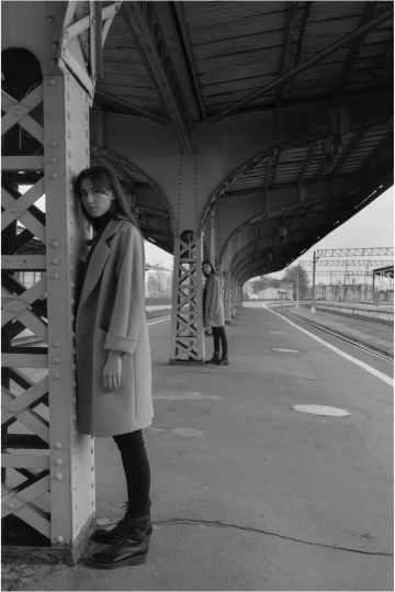 stylish women leaning on pillars on station