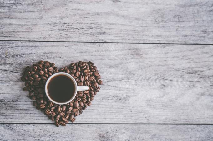 Coffee mug surrounded by coffee beans in the shape of a heart.