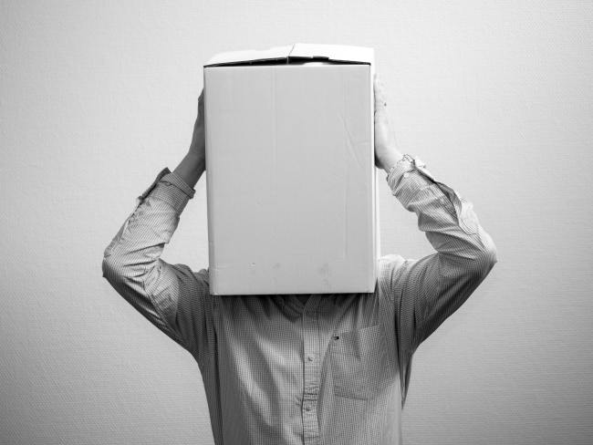 man with head in a box