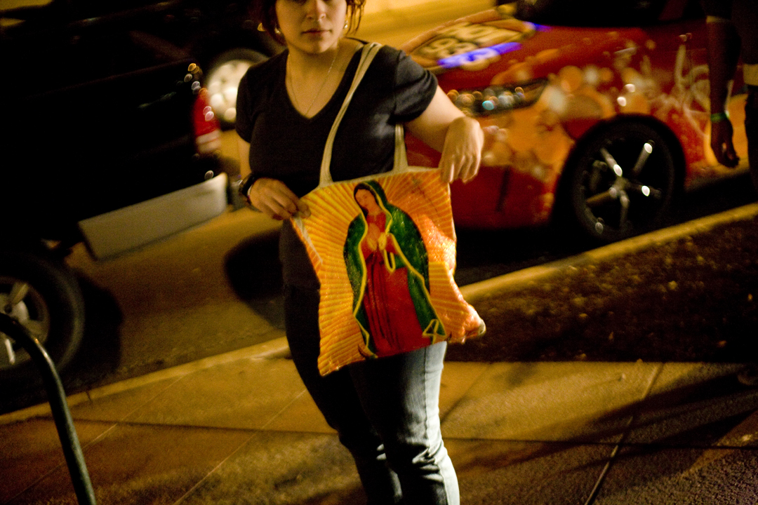 A girl carries a Virgen de Guadalupe purse, representing her heritage rather than faith,  in Austin, Texas.