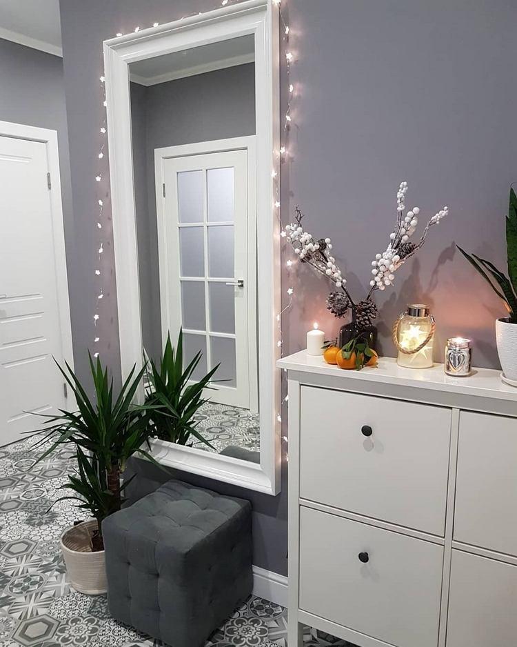 moderne Weihnachtsdeko im Flur mit LED Lichterkette und Beerenzweige auf Schuhschrank
