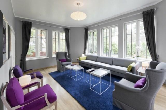 decoration-salon-tapis-bleu-fauteuils-pourpres-canapé-gris-tables-basses-blanches