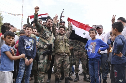 In this photo released by the Syrian official news agency SANA, Syrian troops celebrate and hold the Syrian national flag as…
