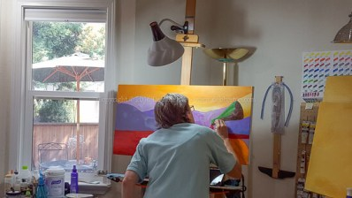 in the art studio working on wine bottle pouring red wine in the hills of sonoma county.