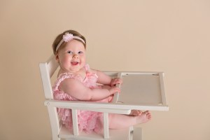 baby girl in pink high chair