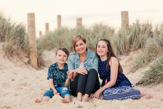 mum sitting in sand dunes with son and daughter