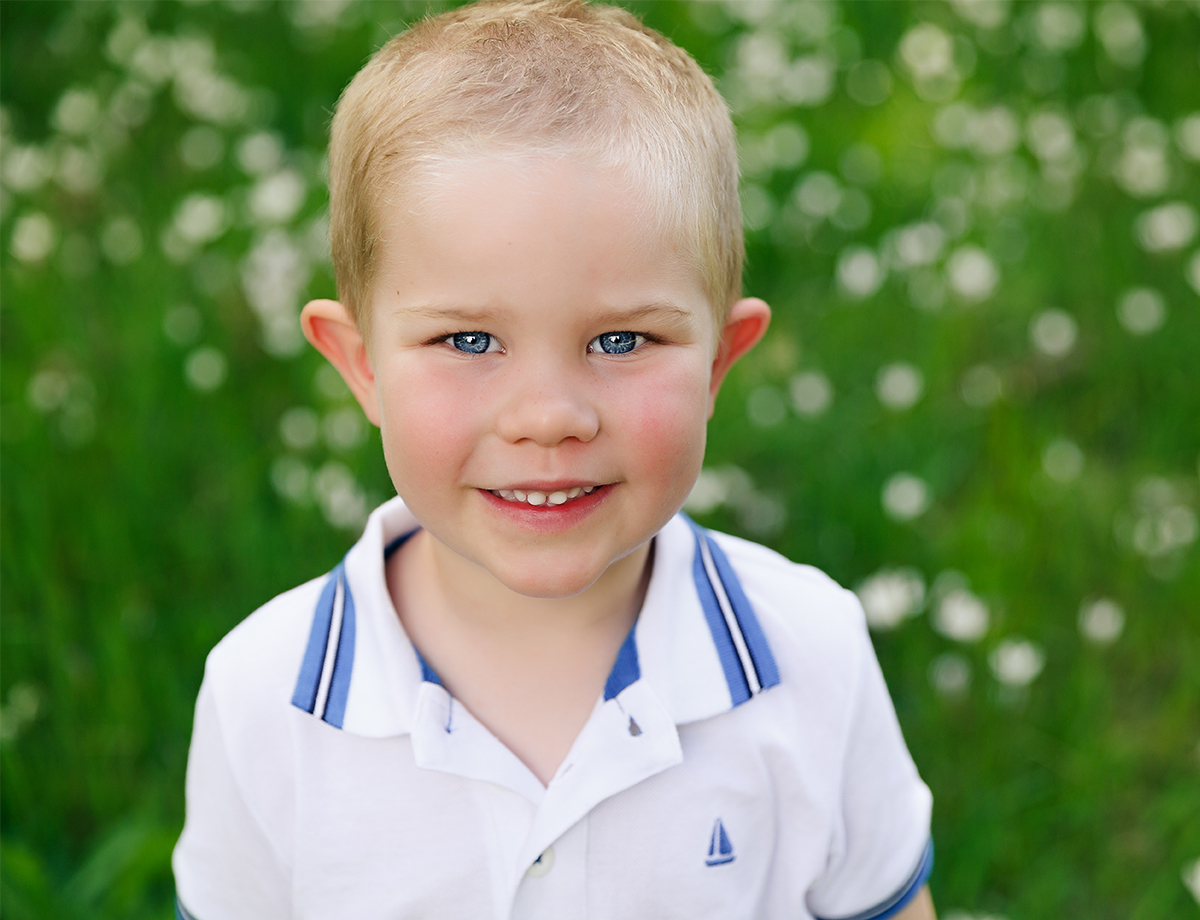 cute boy smiling at his family photo session in the forest in spring by deb elton photography