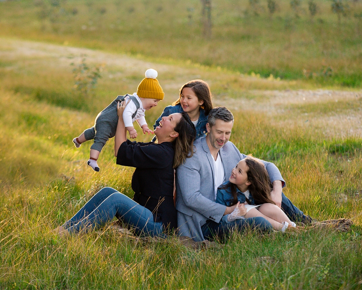 family laughing sitting on a rug in lush grass for family portraits by deb elton photography