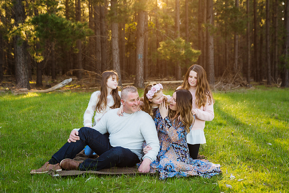 family sitting on a rug in the forest for a family photo session