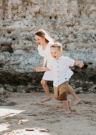 boy and girl running at the beach near rocks