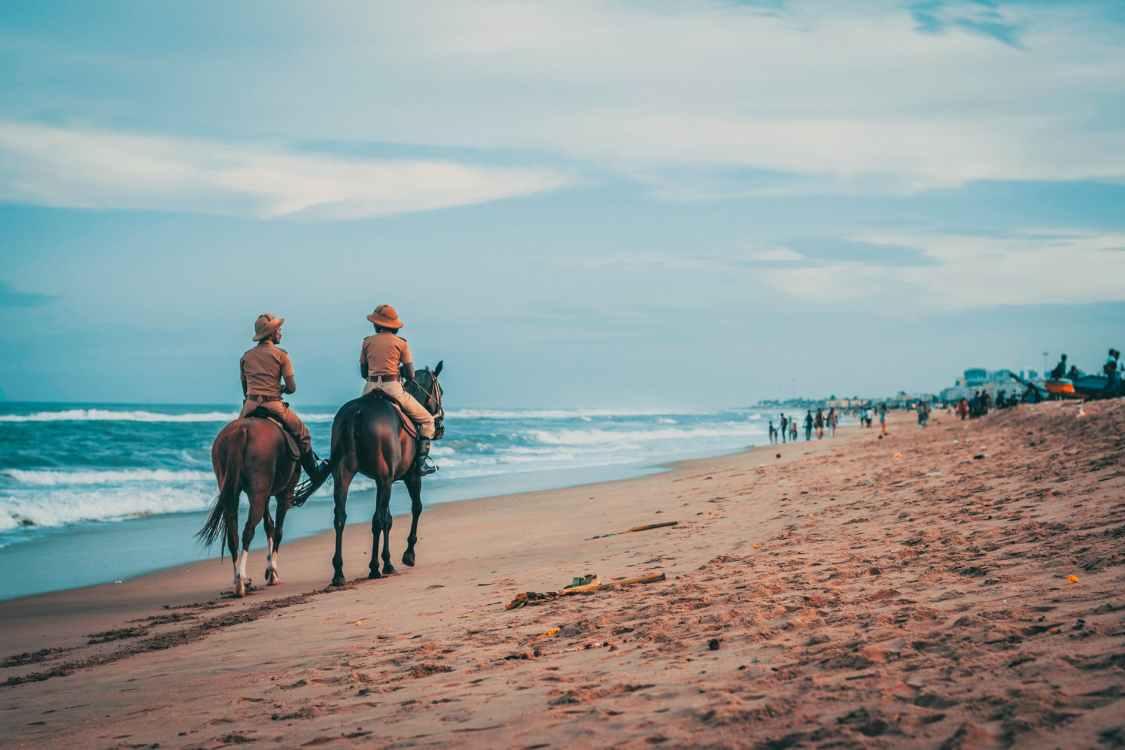 photo of men riding beside sea