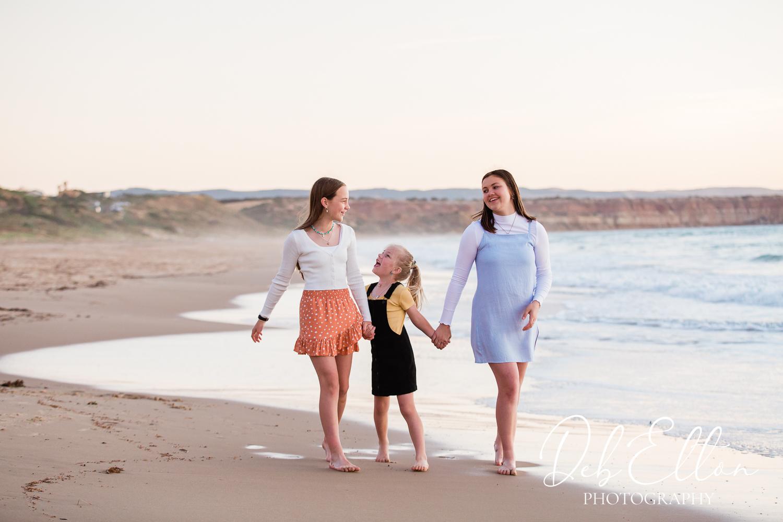 3 girls walking along the beach at sunset