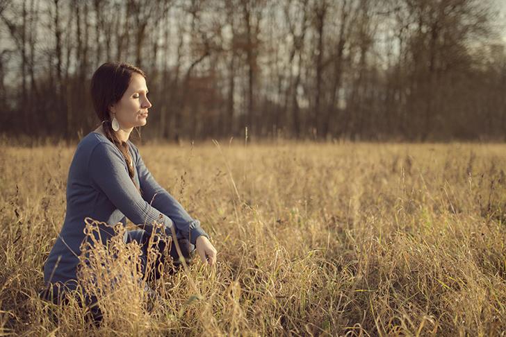 Deutschland, Bayern, Junge Frau sitzt im herbstlichen Gras einer Auenlandschaft und genießt die Sonne