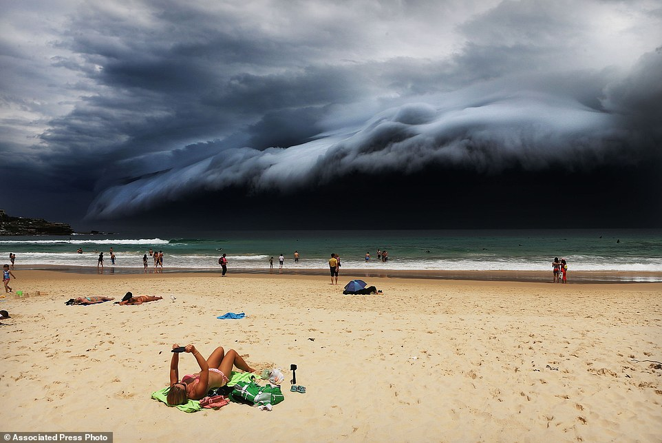 "In this image released by World Press Photo titled ""Storm Front on Bondi Beach"" by photographer Rohan Kelly for the Daily Telegraph which won first prize in the Nature singles category shows a massive cloud tsunami looming over Sydney as a sunbather reads, oblivious to the approaching cloud on Bondi Beach, Sydney, Australia, Nov. 6, 2015. (Rohan Kelly/Daily Telegraph, World Press Photo via AP)"