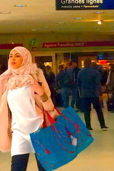 Photo of elegant Muslim woman wearing pink hijab and carrying a blue bag with red handles