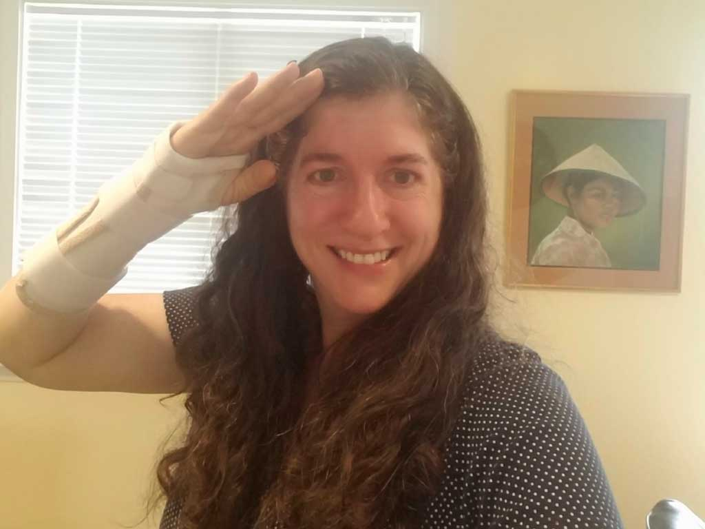 Deborah Munro saluting with cast on right wrist