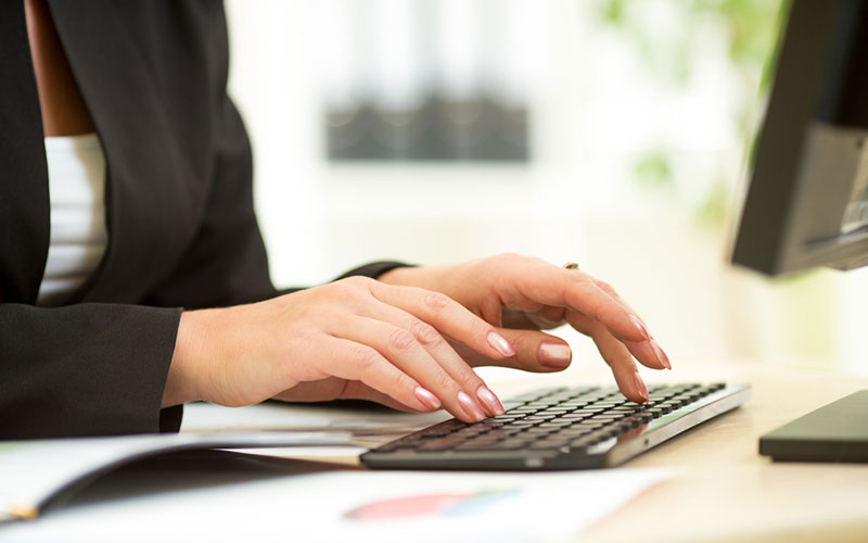 Image of a woman typing on a computer keyboard