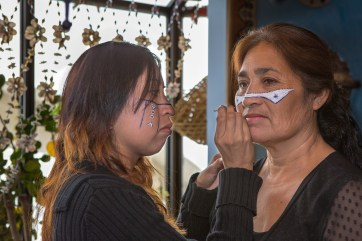 Gabriela Molina applies facepaint to Carmen Moreno, her mother