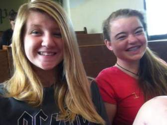 Two happy teenage girls seated in church.