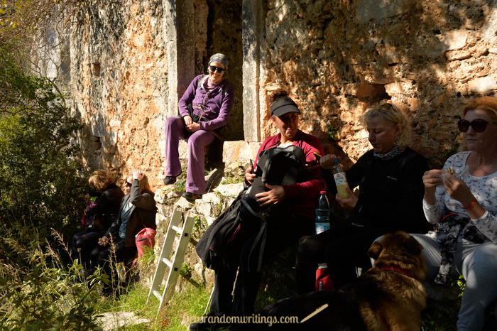 A group of hikers picnicking outside the church in the cave on Zakynthos.