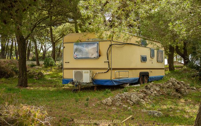 A yellow caravan under some trees on Zakynthos.