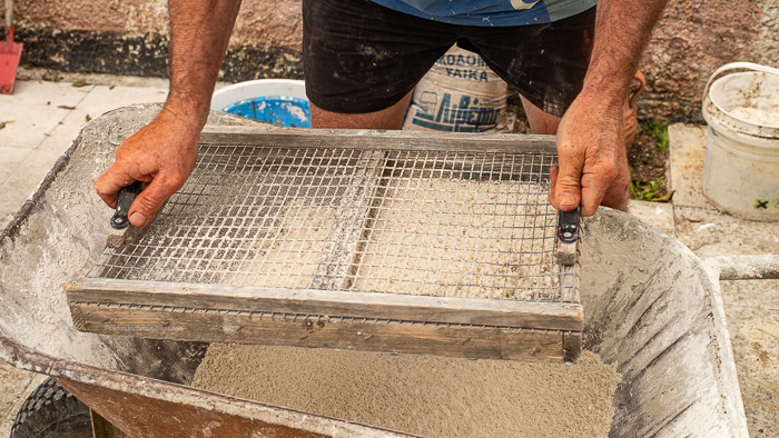 Concrete being sieved into a wheel barrow to make a concrete flower pot.