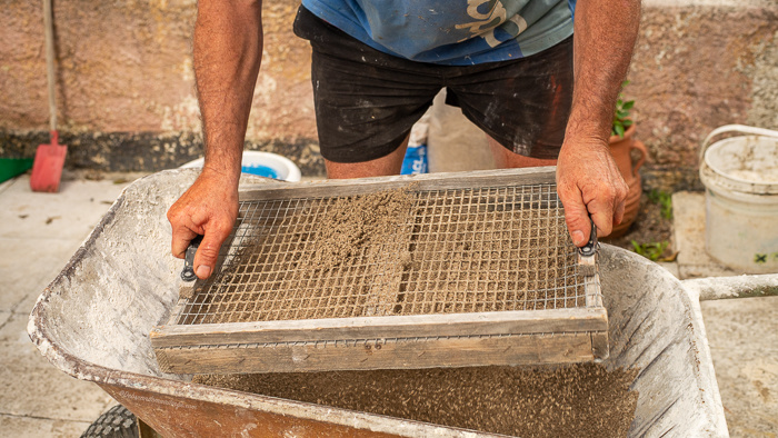 Building sand being sieved into a wheelbarrow full of concrete to make a concrete flower pot.