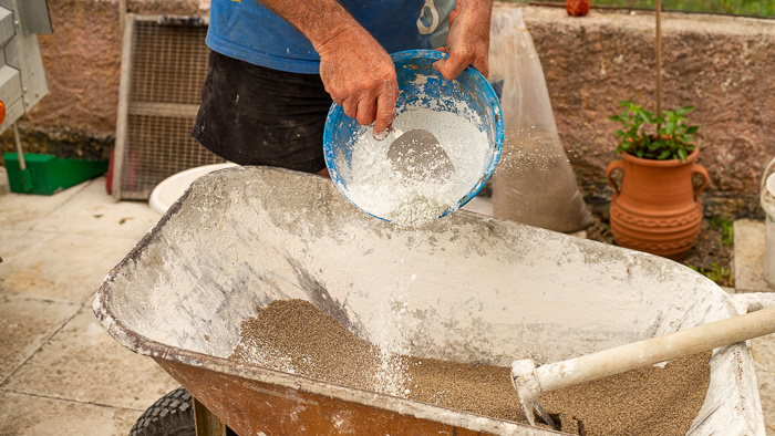 Marble dust being added to concrete in and river sand in a wheel barrow to make a concrete flower pot.