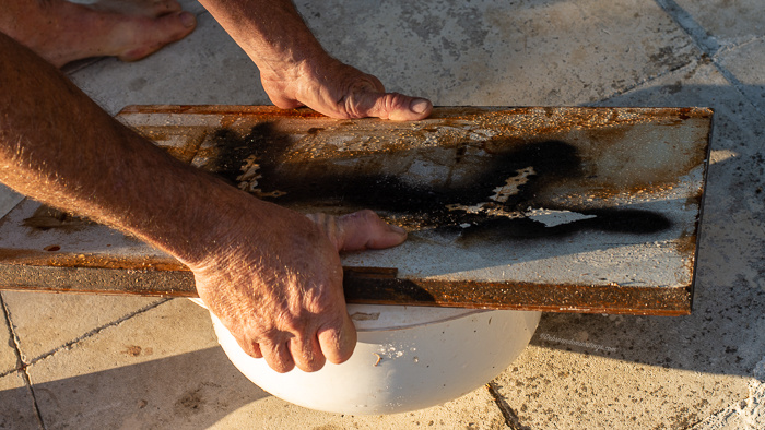 A piece of wood is placed over a bowl to support the pot as it is turned out. Rather similar to turning out a cake.