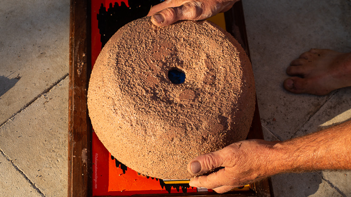 A homemade concrete pot is removed from its outer mould.