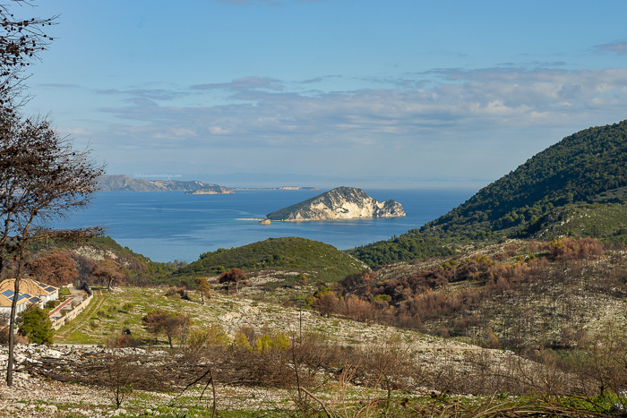 A view of Marathonisi (Turtle Island)off the coast of Zakynthos. A few dead trees. Green trees. Blue sea. Blue sky. Clouds.