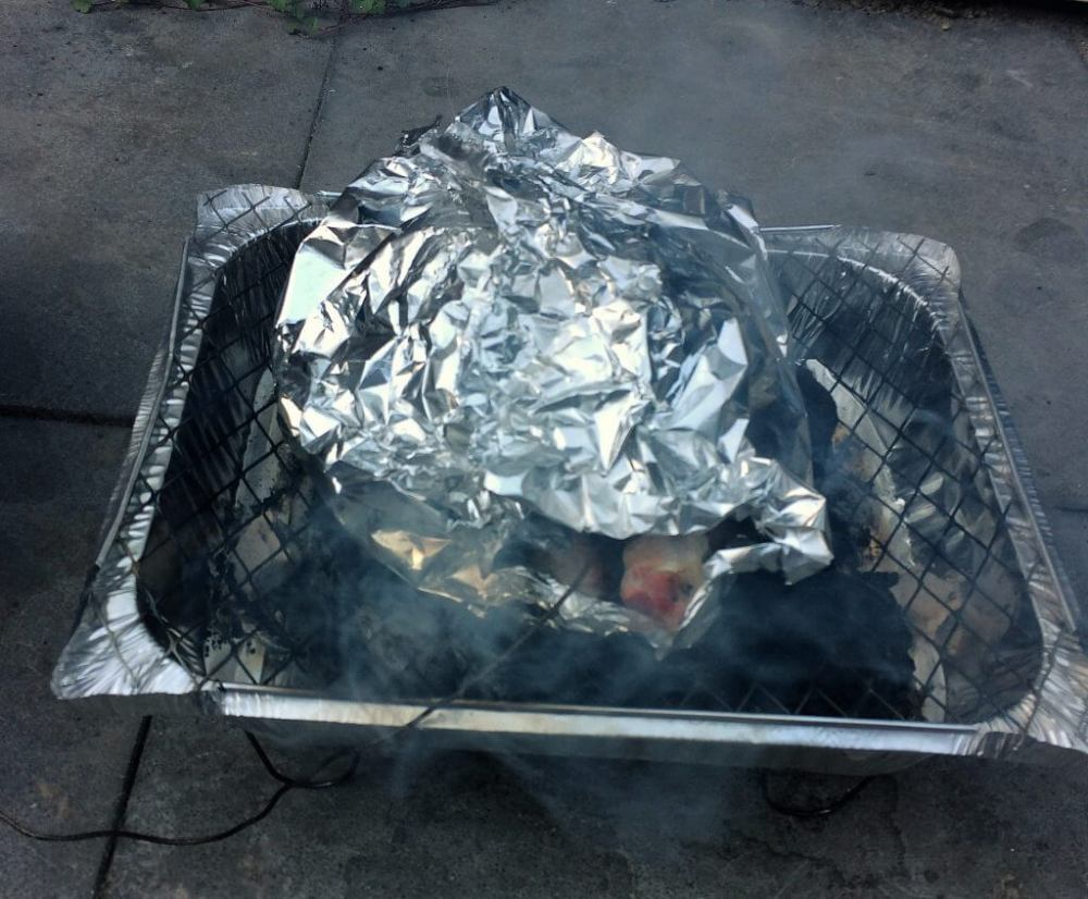 hele kip op een wegwerpbarbecue