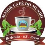 """Desenho de uma xícara de café com fumaça saindo, rodeada de folhas. O desenho tem um circulo de fundo, com os dizeres """"Maior café do mundo"""" e, sob a xícara, uma faixa com as palavras """"Brejetuba - ES - Brasil""""."""